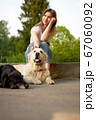 Pensive girl squatting next to dog on summer day. 67060092