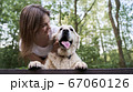 Happy woman with dog standing on bridge among forest on summer day 67060126