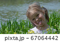 Portrait of a smiling little girl in the grass 67064442