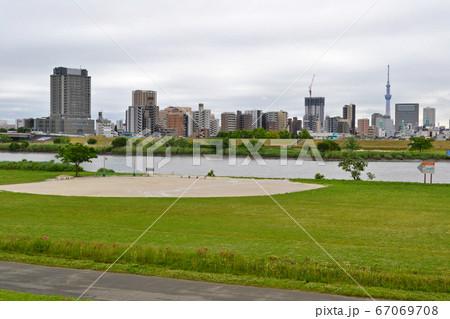 荒川河川敷野球場と足立区千住(国道4号線沿い)のマンション群と街並の景色 67069708