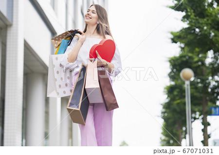 たくさんの買い物袋を抱える女性 67071031