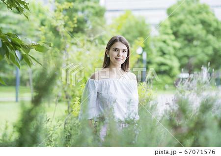 リラックスした表情で公園を散歩する若い女性 67071576