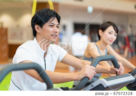 スポーツジムでエアロバイクをするカップル 67072528