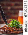 beef steak with sauce and salad, served with beer, product photography 67101272