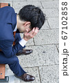 ベンチに座って頭を抱えるビジネスマン 横浜みなとみらい 67102858