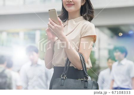 スマホを使うオフィス街にいる日本人ビジネスウーマンのイメージ 67108333
