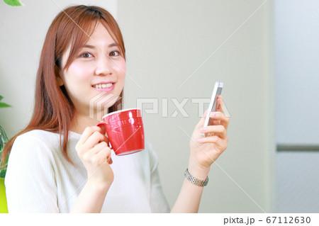 スマホとコーヒーカップを持つ笑顔の女性 67112630