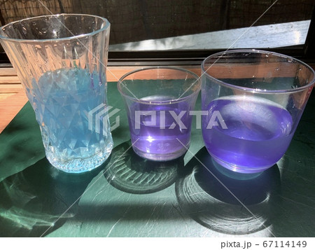 光がさす綺麗な色水の入ったガラスのコップ 67114149