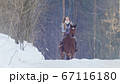 Young female rider riding a black horse through the drifts in the winter frozen forest 67116180