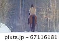 Female rider riding black horse through the snow, rear view 67116181