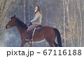 Longhaired female rider wild and fast riding black horse through the snow 67116188