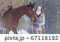 Portrait of beautiful female rider and her black horse in winter field 67116192