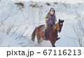 Beautiful longhaired woman riding a brown horse through the deep snowbank in the forst 67116213