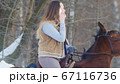 Beautiful female rider use phone in winter field 67116736
