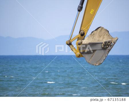 海岸で青空を背景にパワーショベルが砂を掻き取る様子 67135188
