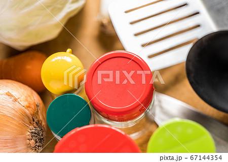 木目のまな板の上にある調味料と調理用具 67144354