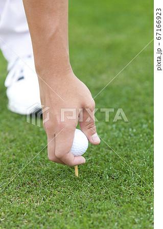 ゴルフボールをセットする男性の手元 67166923