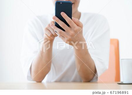 スマホを見ながら会話する若い男性 67196891
