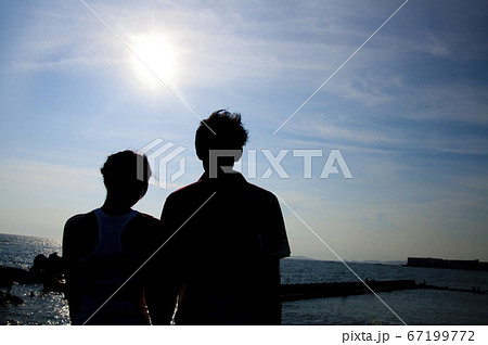 手を繋ぐカップルの後姿のシルエット 67199772