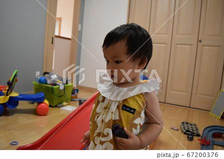 子ども部屋で遊ぶアロハ柄の服を着たかわいい乳児 67200376