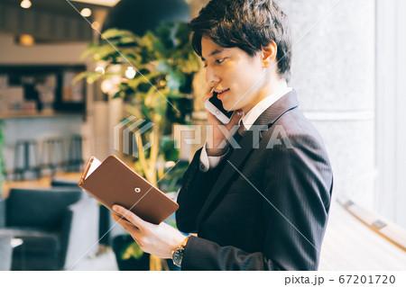手帳を見ながら電話をするビジネスマン 67201720