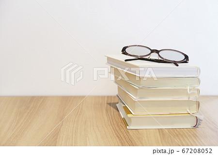 木目の机に積まれた本と眼鏡と白い壁 67208052