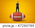 Tiny athletic man in black tracksuit standing on brown oval ball for American football on amber background. 67260789