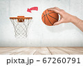Man's hand holding orange basketball ready to throw it into basketball hoop fixed on grungy white wall with red painted arrow pointing at goal. 67260791