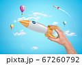 Man's hand holding silver and yellow space rocket against bright blue sky with hot air balloons and one more rocket flying in distance. 67260792