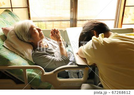 介護ベッドに横たわる年老いた母親と介護に疲れて眠り込む娘 67268612
