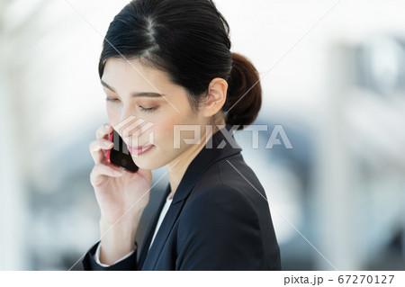スマホで通話するビジネスウーマン【屋外】 67270127