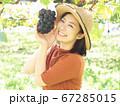 ぶどう園のぶどうに手を添える女性 67285015