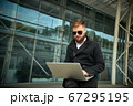 Manager holding laptop, Out of office work, young businessman using computer 67295195