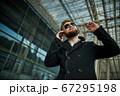 Urban business man in sunglasses talking smart phone traveling walking outside 67295198