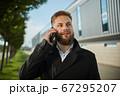 Urban business man talking smart phone traveling walking outside airport 67295207