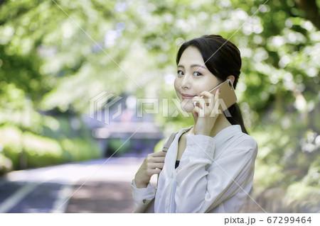 新緑の木々の中スマホを使用している若い女性 67299464