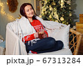 nice woman sits in chair wrapping plaid and drinks beverage 67313284