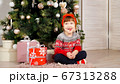kid girl sits under Christmas tree laughing 67313288