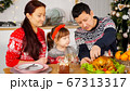 man cuts chicken to feed family sitting at holiday table 67313317