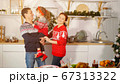 girl kisses father making parents laugh near holiday table 67313322