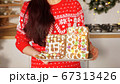 woman holds gingerbread house against Christmas decorations 67313426