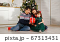 girl child unpacks gift box with parents by Christmas tree 67313431