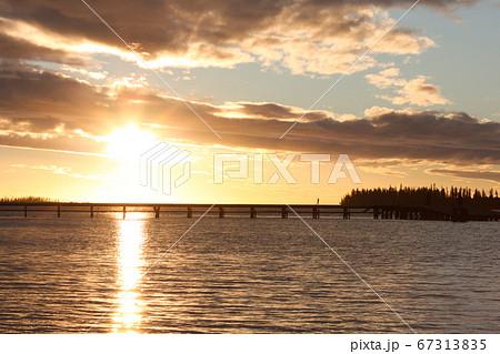 夕日を背景に島に続く橋をジョギングして渡る女性 67313835