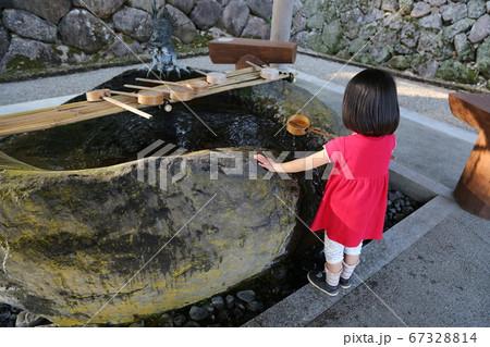 神社の手水舎で手を清める赤い服の女の子 67328814
