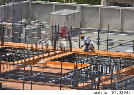 新築マンション 空調ベスト着用し墨だし作業中の型枠大工さん 67332949