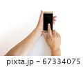 スマートフォンの画面をタップする中年男性の手 67334075