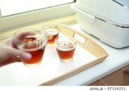 台所でキッチントレイに冷茶を乗せる主婦 67334251