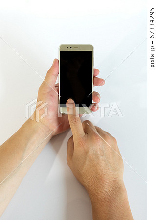 スマートフォンの画面をタップする中年男性の手 67334295