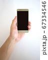 スマートフォンを持つ中年男性の手 67334546