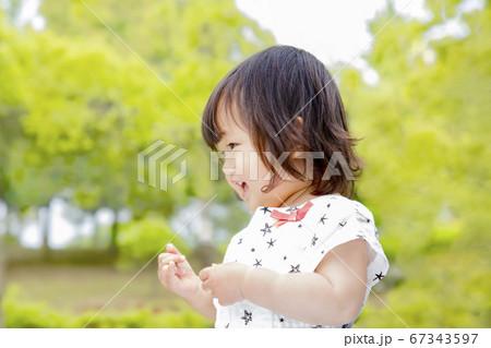 新緑の木々を背景に笑顔で踊る幼い女の子の横姿 67343597